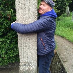 Gísli Einarsson faðmar granítkrossinn í Glendalough. Sögn er bundin við krossinn að nái maður þannig utan um hann að fingurgómar löngutangar snertist, þá munu allir þínir draumar rætast. Gísli fór létt með það.